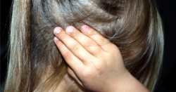 girl covering her ear with her hand