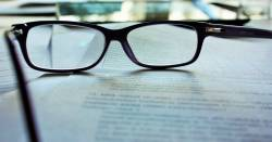 pair of glasses resting on a stack of papers