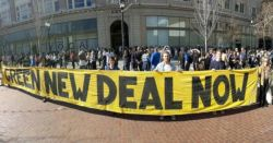 several people holding a large yellow sign with black letters stating GREEN NEW DEAL NOW