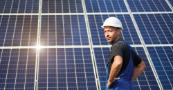 man in hard hat standing in front of a solar panel array