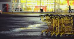 row of yellow grocery carts in front of a grocery store at night