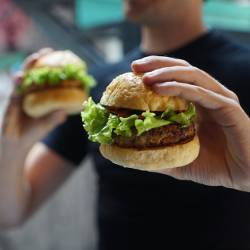 person holding two hamburgers in their hands