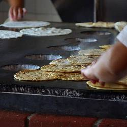 people cooking handmade tortillas