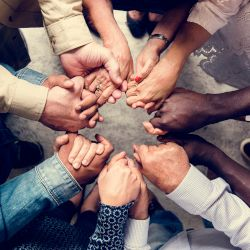 many hands coming together in a circle in teamwork
