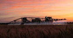 tractor on a farm field spraying pesticides on to a crop at sunset