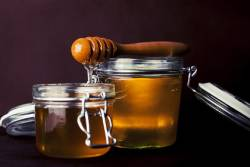 Jars of honey with a dipper