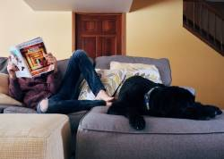 Relaxing at home with the dog and reading a magazine