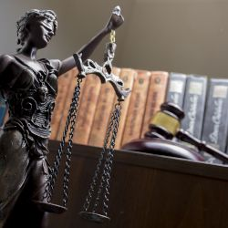 statue of a blindfolded lady justice with scales in front of law books and a judges gavel