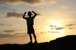 Child at sunrise in victory pose