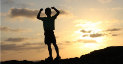 silhouette of kid standing on rock with hands in air
