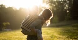 two children playing piggyback in a grassy field at sunset