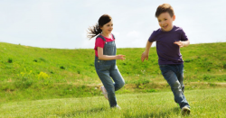 two children running through a grassy field