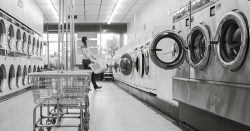 Someone doing laundry at a laundromat