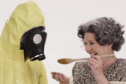 Mama Monsanto serving a taste of food to a person in a biohazard suit