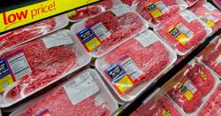 packages of ground beef and meat in a meat cooler at a grocery store