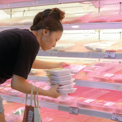 woman shopping for meat in a grocery store