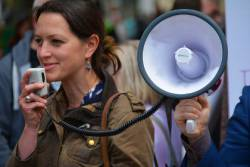 Woman at a protest march speaking through a megaphone