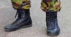 feet of a military soldier wearing black leather combat boots