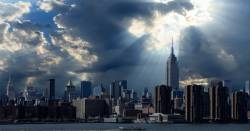 rays of sunshine pouring through clouds on the New York City skyline