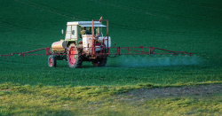 Farmer spraying pesticides with a tractor..