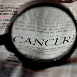magnifying glass over a newspaper with the word CANCER
