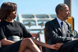 Michelle Obama and President Obama hold hands during an event