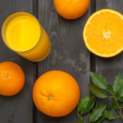 orange juice in a glass surrounded by fresh oranges with leaves