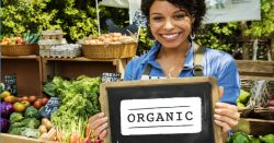 woman at a farmers market holding a sign reading ORGANIC