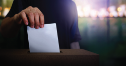 Person voting with a paper ballot.