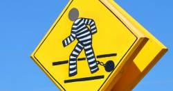 Yellow pedestrian crossing sign painted to look like a prisoner with ball and chain