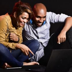 two people sitting beside each other watching a laptop computer screen