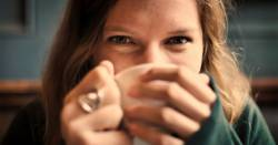 woman drinking a hot beverage out of a white ceramic mug