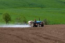 Farm tractor spreading chemical onto farmland in preparation for planting