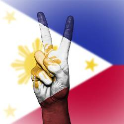 projection of the Philippines flag over a hand with a peace sign