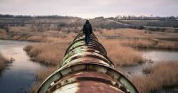 Person walking along a rusted pipeline in a wetland