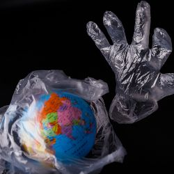 planet earth wrapped in a plastic bag and a plastic glove