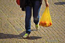 Person walking with a plastic shopping bag