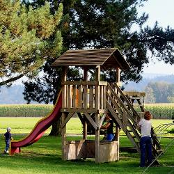 children playing on a playground outside next to a corn field during the day