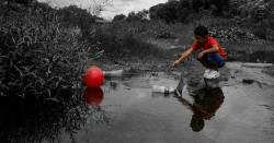 young child on the edge of a river reaching over pollution and litter to grasp a red ball