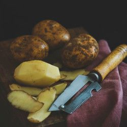 pile of potatoes on a table cloth with a peeler
