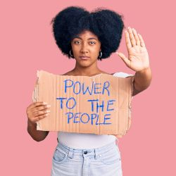 young woman with her hand up holding a cardboard sign stating POWER TO THE PEOPLE