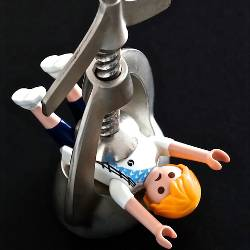 Toy person in a vice grip being squeezed