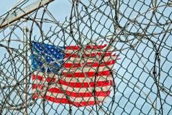 Tattered American flag behind barbed wire and a chain link fence