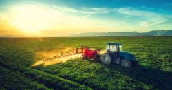 red and blue tractor spraying on a farm crop field at sunset
