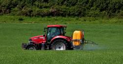 red farm tractor spraying pesticide on crop field