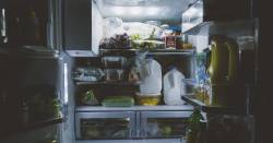 illuminated refrigerator in a dark kitchen full of produce and packaged food