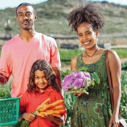 family at a farm holding a harvest of organic vegetables