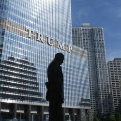 silhouette of a statue in front of Trump tower building