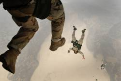 military personnel skydiving out of an airplane