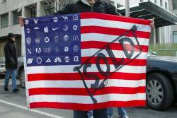Protester holding Adbusters Corporate American Flag at Bush's 2nd inauguration, Washington DC.